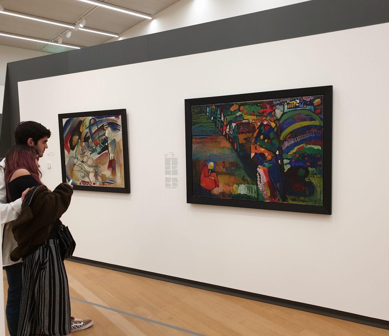 una paerja observa cuadro en la pared de un museo