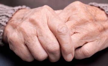 dos manos de persona mayor estrechadas