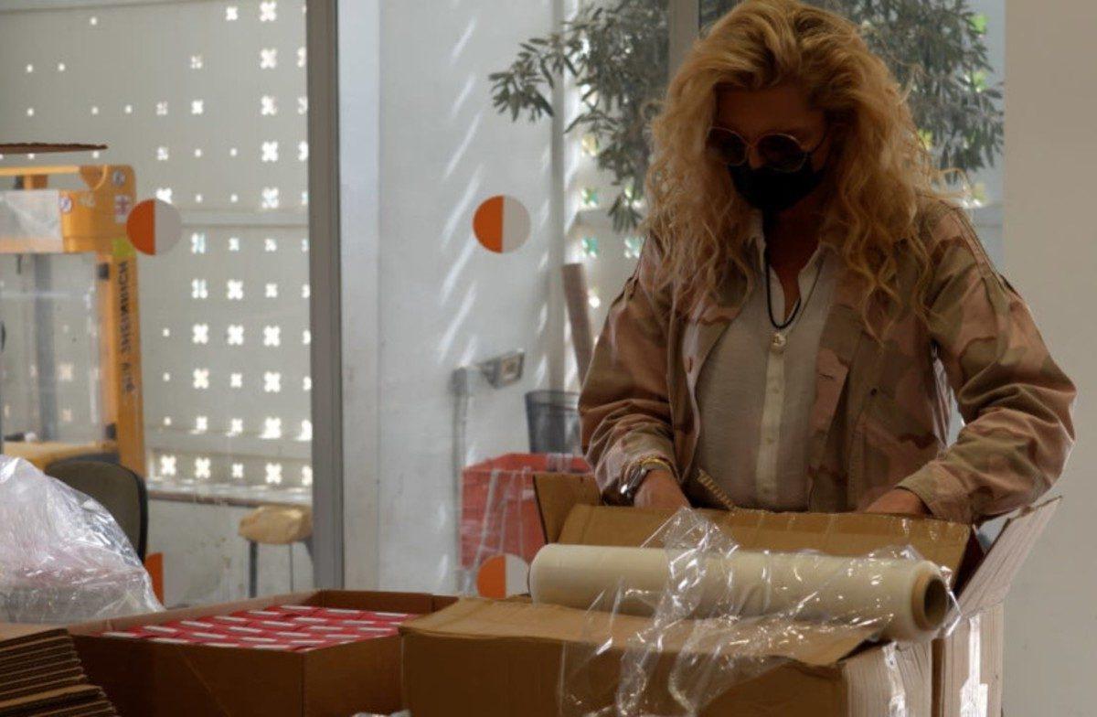 mujer con cabellera rubia y máscara facial prepara paquetes