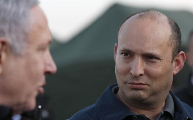 Dos caras. A la izquierda, habla un hombre canoso de perfil, a la derecha un hombre calvo lo mira con atención