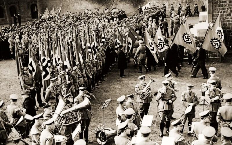 soldados nazis con banderas con la esvástica reunidos en una plaza y la orquesta militar nazi