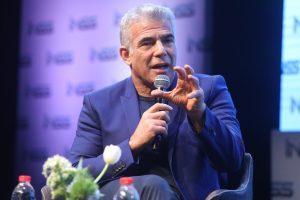 hombre canoso sentado habla ante un micrófono gesticulando con la mano izquierda