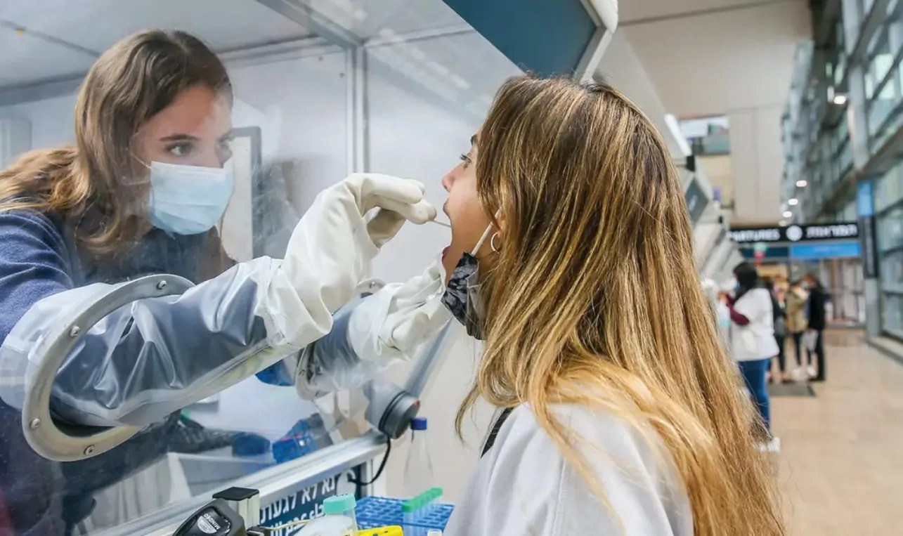 Laboratorista toma muestra nasofaringea para COVID-19 a una persona en Israel