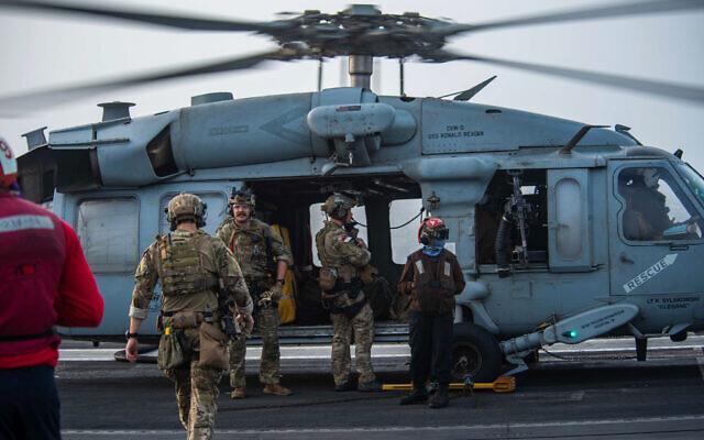 En esta foto proporcionada por la Marina de los Estados Unidos, los marineros asignados a una unidad de artefactos explosivos abordan un helicóptero MH-60S Seahawk en la cubierta de vuelo del portaaviones USS Ronald Reagan para dirigirse a un petrolero que fue atacado frente a las costas de Omán en Arabia. Sea, el 30 de julio de 2021.