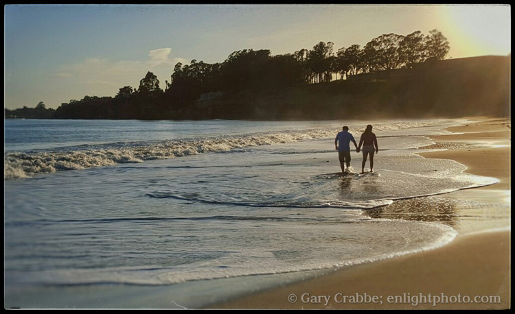 Image: Couple walking on beach at sunset, New Brighton State Park, California