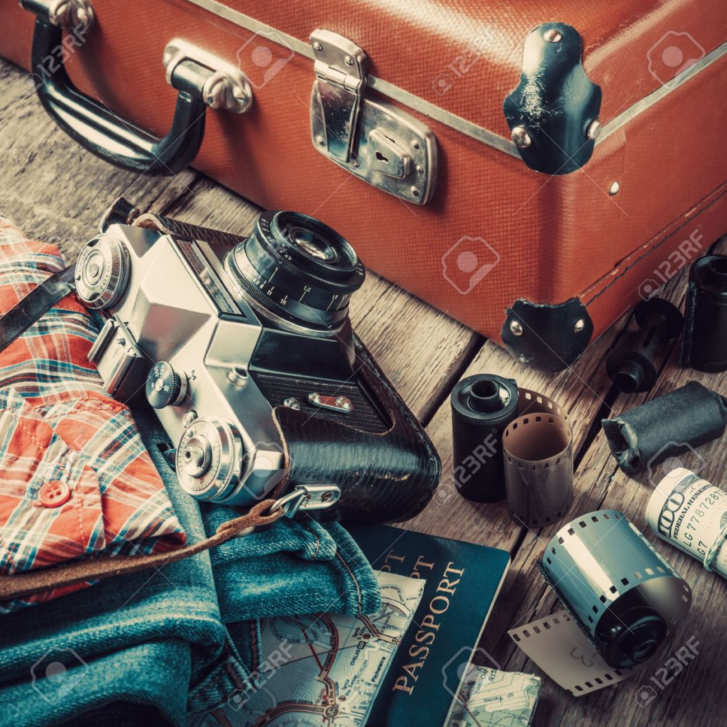 Old travel suitcase, sneakers, clothing, map, filmstrip and retro film camera on wooden background. Vintage stylized.