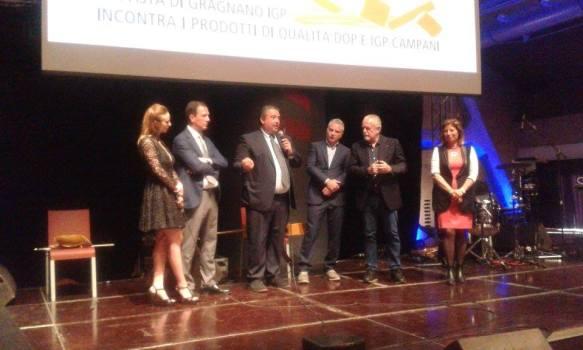 L'immagine può contenere: 5 persone, persone sul palco, persone in piedi, vestito elegante e spazio al chiuso