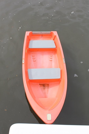 Orange plastic dinghy tied to the houseboat.