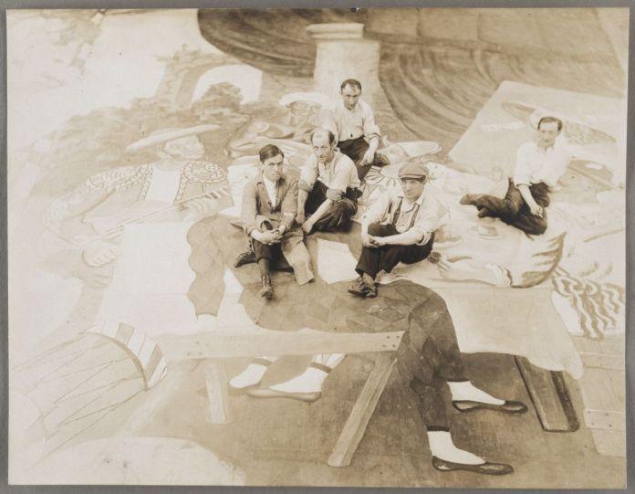 """Picasso et ses assistants assis sur le rideau de scène """"Parade"""" en cours d'exécution à Montparnasse, en 1917, tirage attribué à Harry B. Lachman. Epreuve gélatino-argentique, 17 x 22 cm Achat, 1998, Musée national Picasso-Paris. MP1998-142 © Succession Picasso 2018 ©Droits réservés (Harry Lachman) - RMN-Grand Palais (Musée national Picasso-Paris) / Franck Raux. Picasso et les Ballets russes, entre Italie et Espagne au Mucem"""