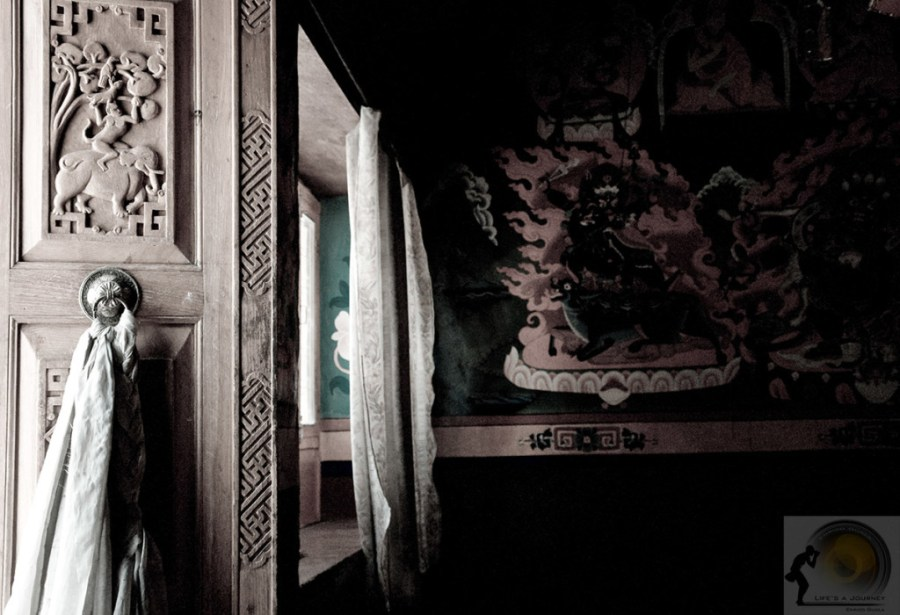 entrata nel DuKhang -sulla porta in legno intarsiato si nota la fiaba dei 4 fratelli in armonia