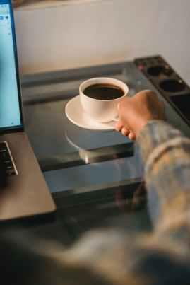 black man drinking coffee while working at laptop