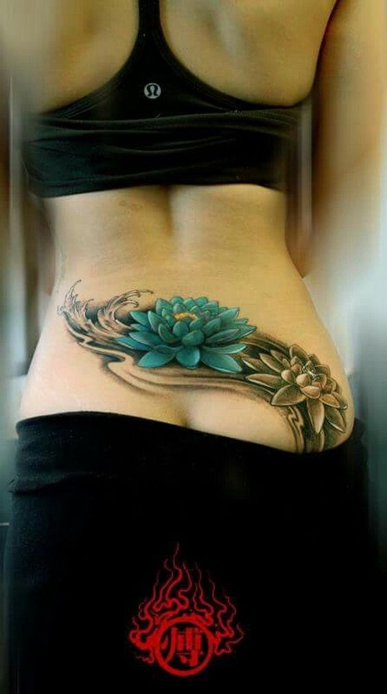 Blue black and white lotus lower back tattoo