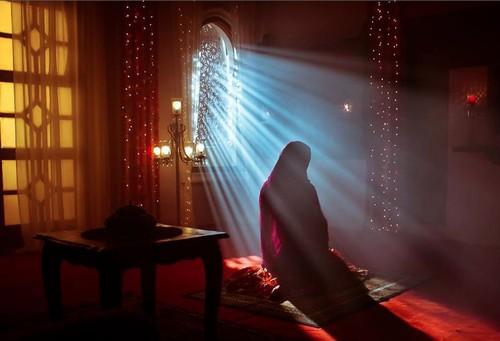 muslim woman praying namaz in rays of light