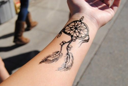 black dreamcatcher tattoo on forearm