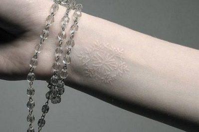 white ink snowflake tattoo on wrist