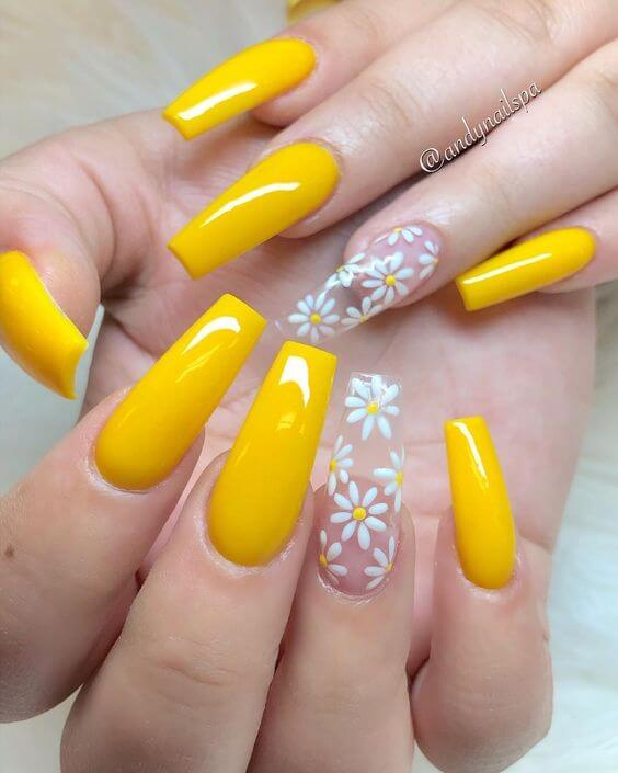 yellow coffin nails with transparent white flowers on one finger