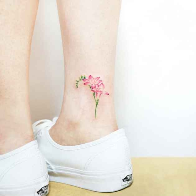 delicate pink freesia flower tattoo on ankle