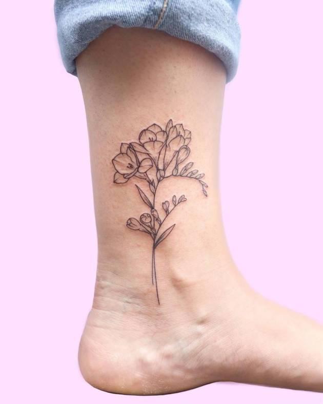 outline freesia flower tattoo design on ankle