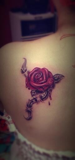 single bleeding rose with thorny vine tattoo design on back shoulder blade