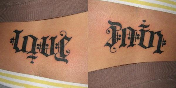 love and pain ambigram tattoos on lower back