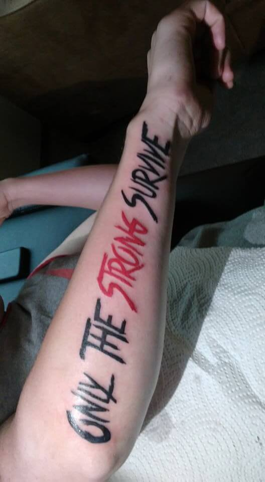 black and red ink only the strong survive quote tattoo design on side forearm