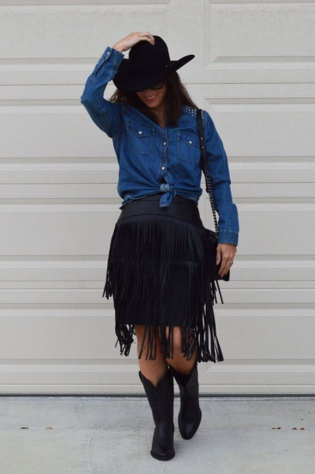 knotted shirt with black fringed skirt paired with hat and boots cowgirl outfit idea