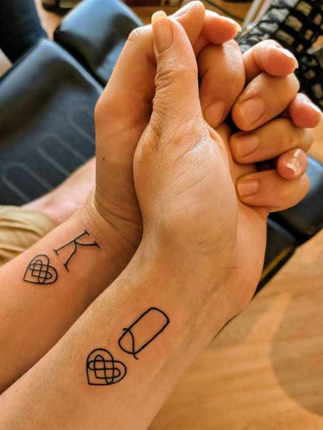 king and queen initials with outline double heart infinity playing card tattoos on wrist for couples
