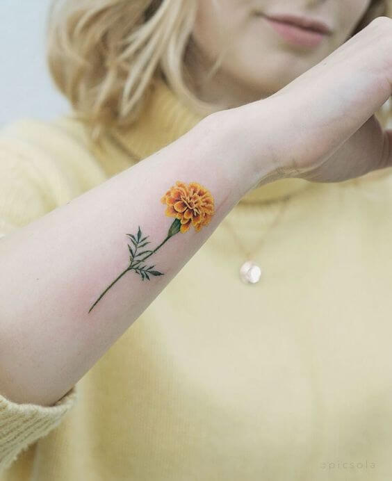 small yellow carnation January birth flower tattoo on side forearm