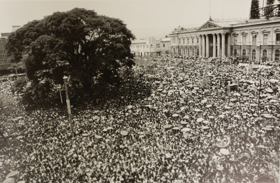Crowd in plaza during funeral mass for Archbishop Romero. Photo from the book El Salvador, published by Writers and Readers Publishing Cooperative, 1983.