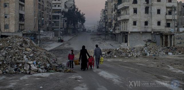Una familia camina por calles vacías de Aleppo. Tratan de vivir una vida en la guerra de una ciudad desgarrada. / Niclas Hammarström