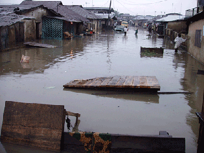 Its not the flood water, but rather washed up planks, appear to create a barrier         along this street at Agege, Lagos.