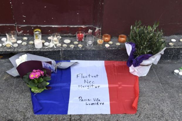"""Flowers, candles and the French national flag with the Latin, """"Tossed but not sunk"""" the motto of Paris written on it, is laid outside of the Carillon, adjacent to the Cambodian restaurant on Rue Alibert in the 10th district, of the French capital Paris, on November 14, 2015, the morning after an attack which killed 12 people at the restaurant. Islamic State jihadists claimed a series of coordinated attacks by suicide bombers and gunmen in the city that killed at least 128 people at a concert hall, restaurants and the national sports stadium. Photo credit: AFP/Dominique Faget/Getty Images"""