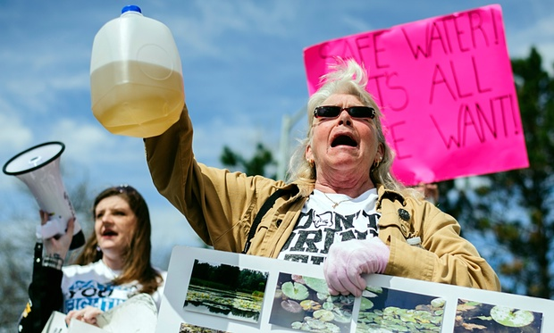 Protesters hold up jugs of discolored water outside the Farmers Market in Flint, marking the one-year anniversary of the city switching from using Detroit water to Flint River water. Photo credit: Sam Owens/AP