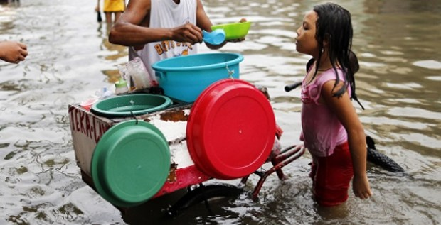 A young Filipino buys food from a vendor on a flooded street in Malabon, north of Manila, Philippines, 08 July 2015. According to the Philippines State weather forecast, heavy rainfall is expected in Metro Manila and nearby provinces due to an enhanced Southwest Monsoon and Tropical Storm Linfa, Typhoon Chan-hom and Typhoon Nangka which are lining up across the Pacific Ocean. Photo credit: EPA/FRANCIS R MALASIG  60 million people endangered as El Niño threatens el nino weather630