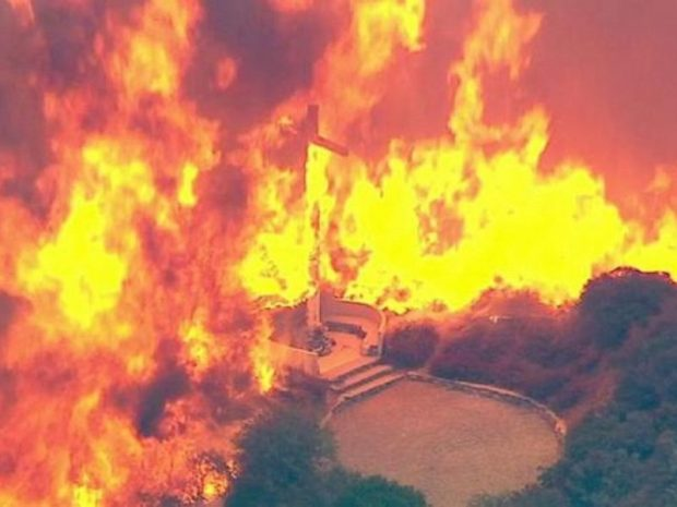 A cross burns in the Blue Cut Fire in the San Bernardino National Forest above Devore on Tuesday, Aug. 16, 2016.  82,000 evacuated over wildfire near Los Angeles Fire e1471467688127