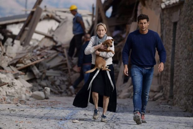 A woman holds a dog in her arms as she walks with a man next to the rubble of buildings in Amatrice. Photo credit: Filippo Monteforte/AFP/Getty  Images: Devastating quake rattles central Italy Italy6 e1472099527330