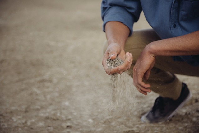 Researcher squatting letting sand fall through his fingers