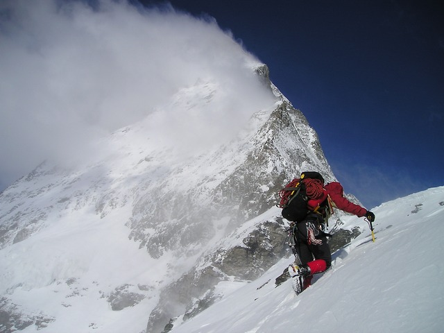Researcher climbing a snowy mountain while snow blows off a mountain in the distance