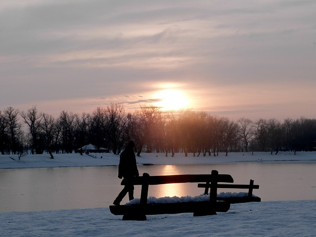 Ice covered lake with the sun reflecting off the surface, a bench in front of the lake in the snow with a person walking next to it
