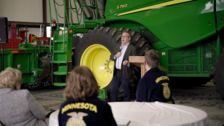 photo of Wheeler spaking to an audience and a large green tractor