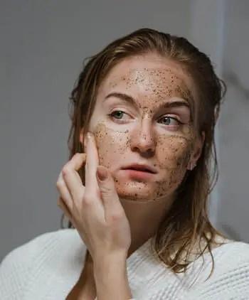 person adding cream to face