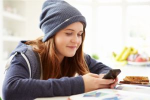 Teenage Girl Sending Text Message Whilst Studying