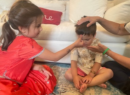 Girl blesses her brother by putting her thumb on his forehead.