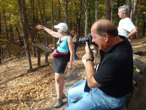 A man takes a photo in the Richard T. Anderson Conservation Area while a woman talks about the big woods forest there.