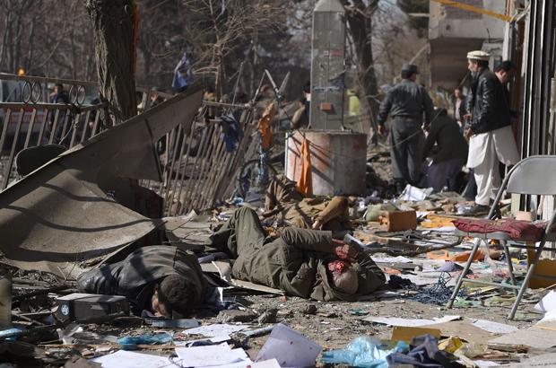 Voluntários afegãos carregam os corpos das vítimas de um carro-bomba que explodiu em frente do edifício do Ministério do Interior em Cabul, no Afeganistão, em 27 de janeiro de 2018. Uma ambulância cheia de explosivos detonou numa área lotada de pessoas em Cabul em 27 de janeiro, matando pelo menos 17 e ferindo outras 110, disseram as autoridades, num ataque que foi reivindicado pelo talibã (Wakil Kohsar/AFP/Getty Images)
