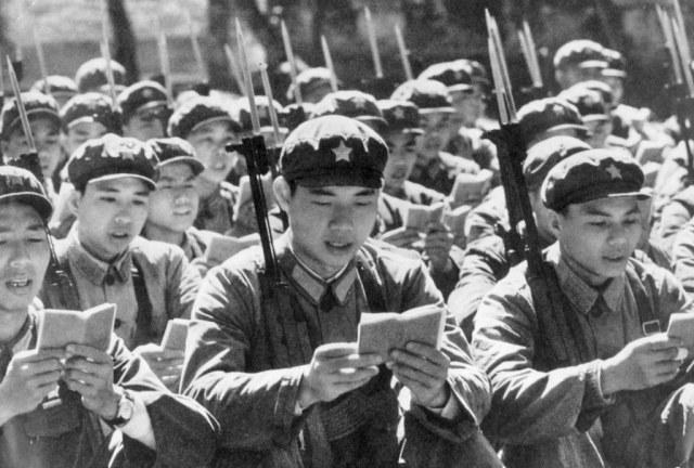 """Guardas Vermelhos chineses leem o pequeno livro """"Citações do Presidente Mao Tsé-tung"""" antes de começar o dia, por volta de 1970 (Keystone/Getty Images)"""