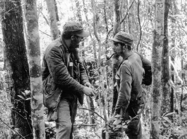 """Foto de 8 de outubro de 1957 mostra o líder cubano Fidel Castro (esq.) conversando com Ernesto """"Che"""" Guevara (dir.) na floresta da Sierra Maestra, em Cuba (Arquivo/AFP/Getty Images)"""