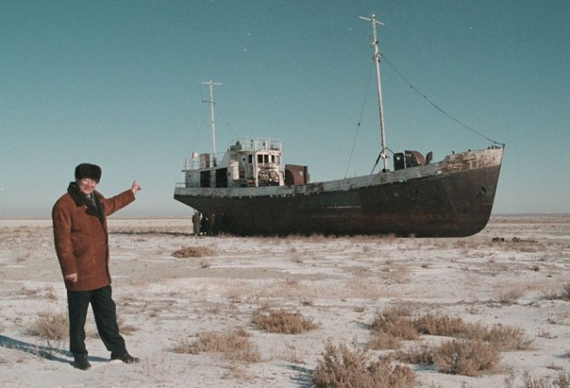 Aralsk's Mayor Alashbai Baimyrzayev points 23 March 1999 near the city of Kyzmet, a fishery on Aralsk's dry harbor at an abandoned fishermen ship in Aral Sea. Aral Sea, an inland sea, East of the Caspian Sea, mainly in Kazakhstan is world's fourth largest lake. Originally 65,000 sq km/25,000 sq mi, 420 km/260 mi long, 280 km/175 mi wide, maximum depth 70 m/230 ft, Aral Sea contains several small island. The diversion of water from rivers supplying the sea for cotton irrigation projects has seriously upset ecological balance and the sea shrank by nearly three-fourths an dropped 19 meters over three decades. / AFP / STRINGER (Photo credit should read STRINGER/AFP/Getty Images)