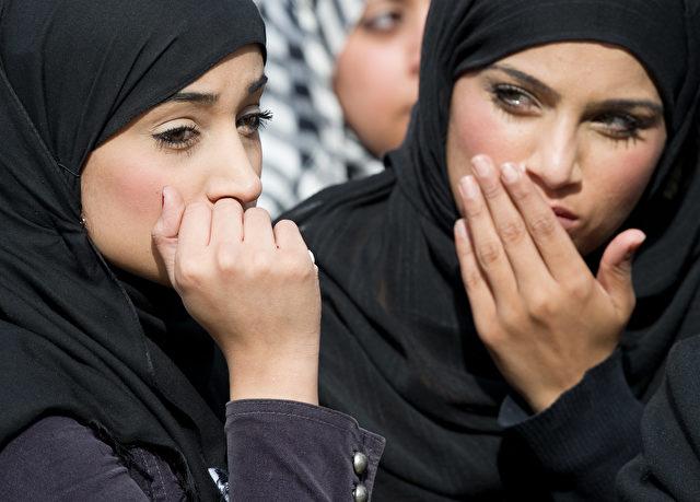 Diese beiden Frauen gehören nicht zu dem Urteil des Landesgerichtes. Jedoch sind Bilder von muslimischen Hochzeiten kaum findbar. Die beiden schauen in Winson Green, Birmingham einem Trauerzug zu, als während eines Gebetes 2011 drei Männer getötet wurden. Tausende Trauernde versammelten sich für die moslemischen Begräbnisgebete der Getöteten. Foto: LEON NEAL/AFP/Getty Images