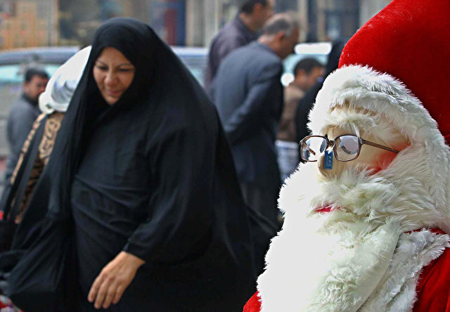 BAGHDAD, IRAQ: An Iraqi muslim woman walks by a Santa Claus doll outside a store in the commercial district of Karada in Baghdad 20 December 2003, as the Iraqi minority catholic community prepares for the first Christmas since the fall of Saddam Hussein. AFP PHOTO/Ahmad AL-RUBAYE (Photo credit should read AHMAD AL-RUBAYE/AFP/Getty Images)